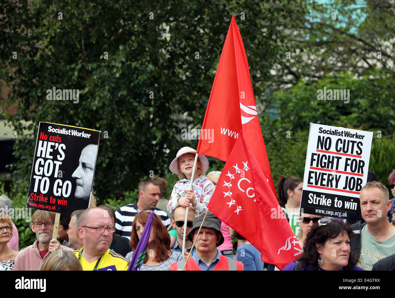 Swansea, UK. 10th July, 2014.  Pictured: A young girl holding a Unite Union flag among two Socialist Workers placards - Stock Image