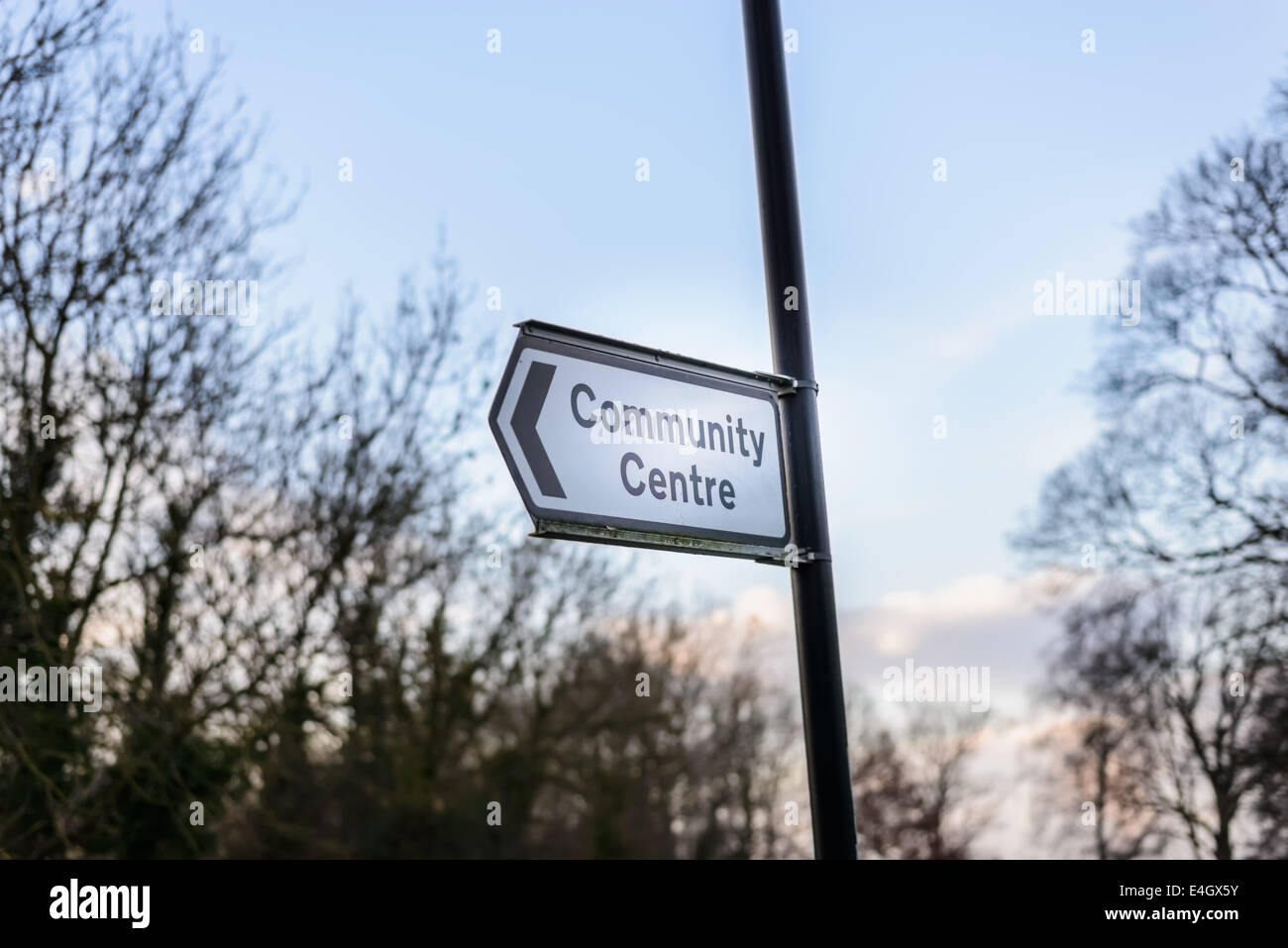 British 'Community Centre' center road sign with arrow, elevated on a post on a road. - Stock Image