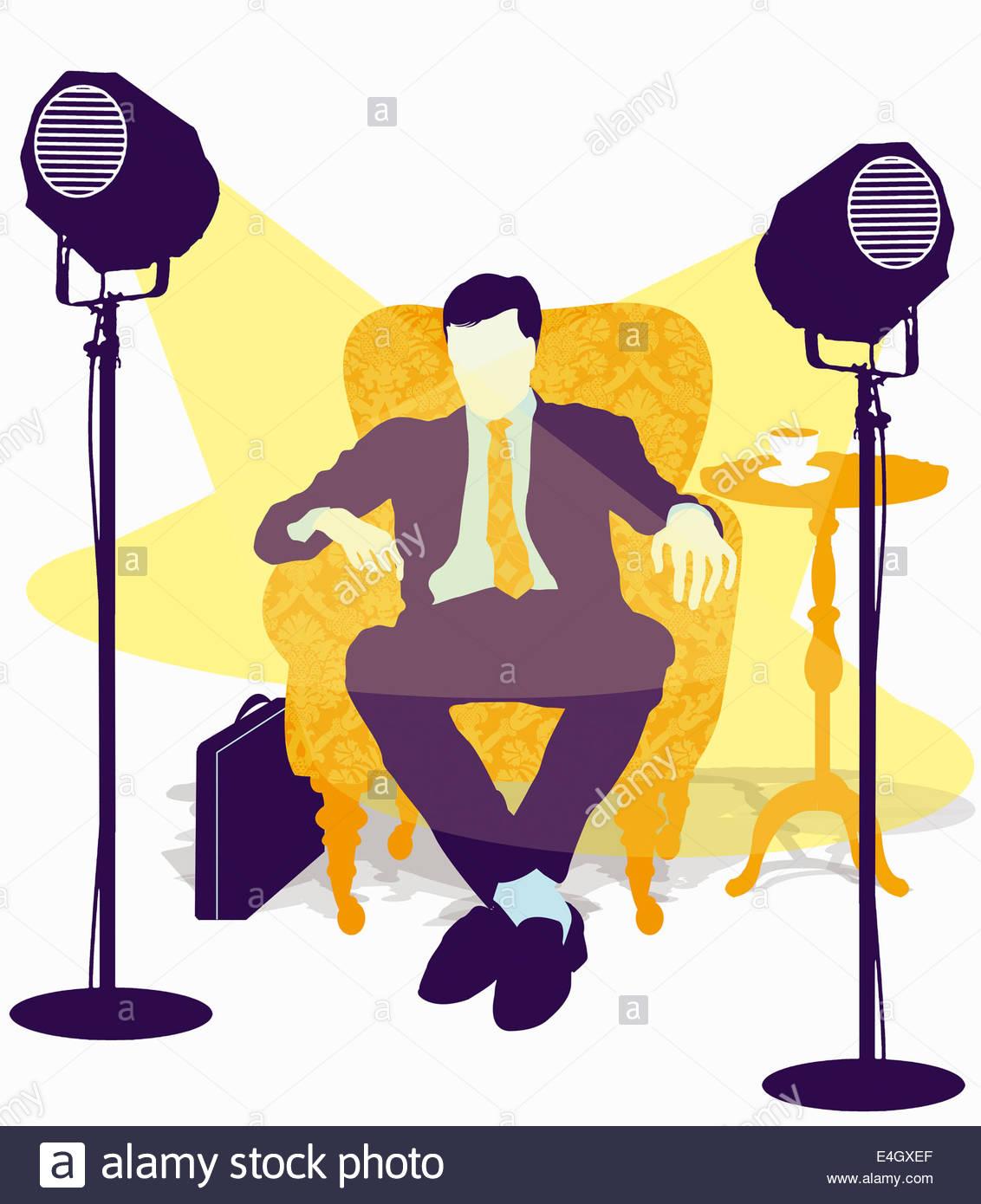 Spotlights on businessman sitting in armchair - Stock Image