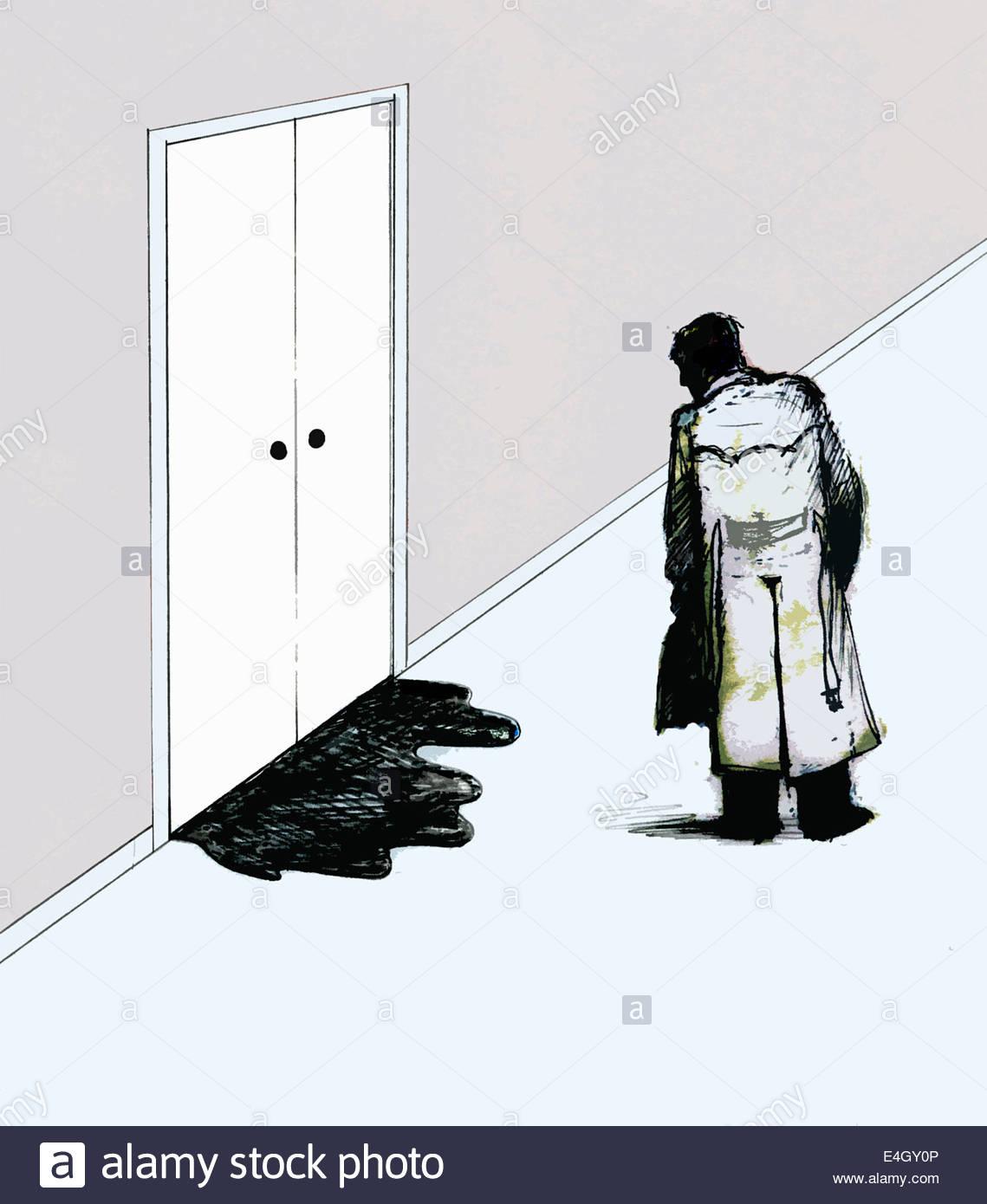 Businessman looking at liquid leaking below closed door - Stock Image