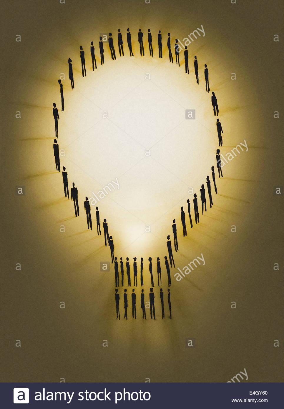 People outlining illuminated light bulb - Stock Image