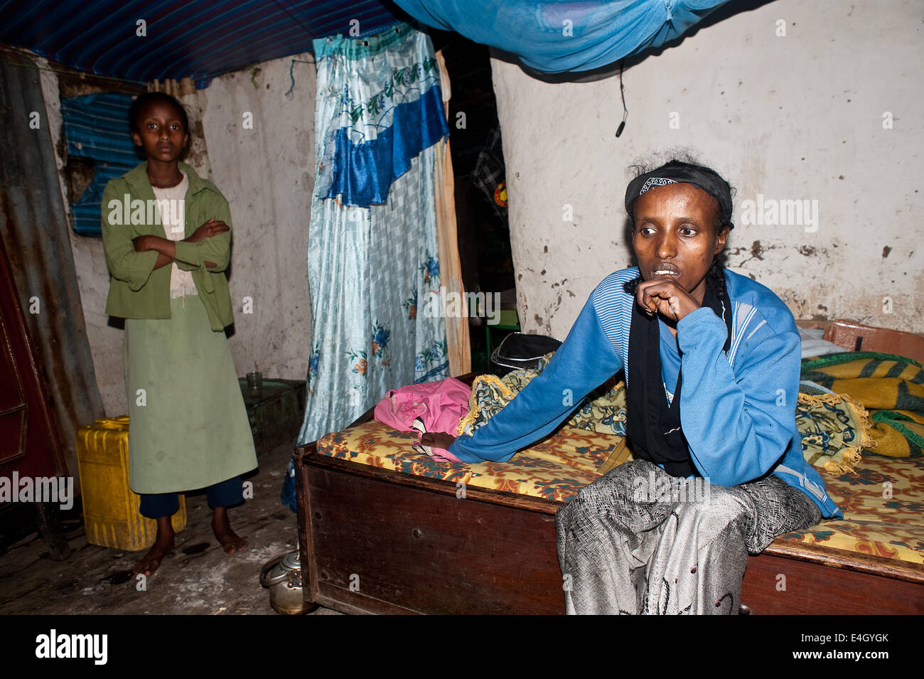Woman suffering from aids at home. In the background, her healthy daughter ( Ethiopia) - Stock Image