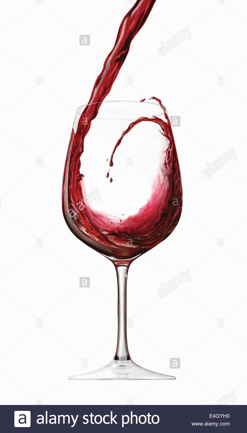 Red wine splashing and swirling into wine glass - Stock Image