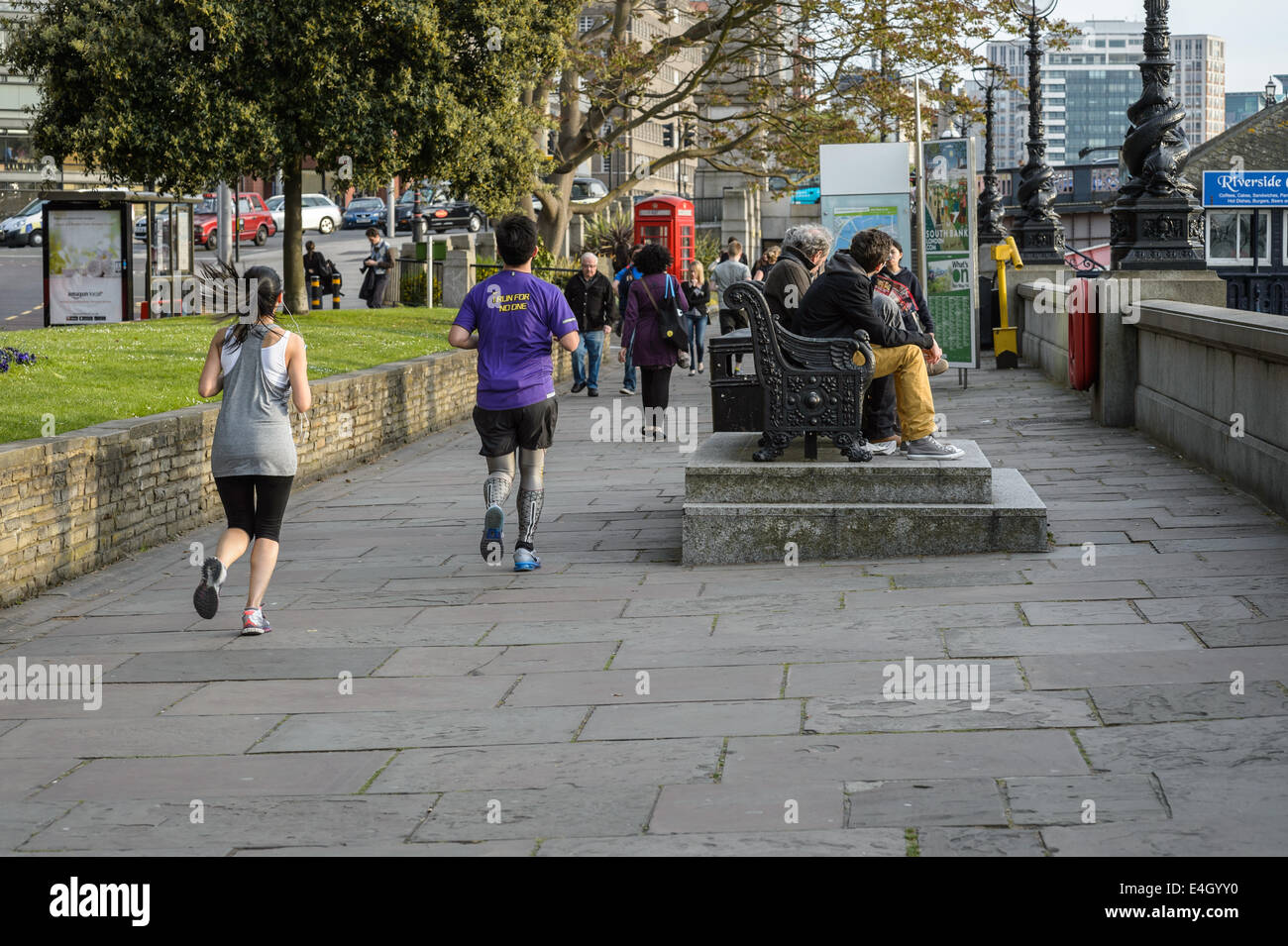 A young woman female and man male running along the River Thames on a Spring evening after work, London UK Stock Photo