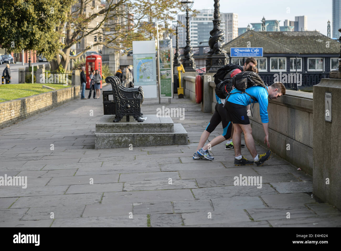 Joggers runners warm down stretch on a run home from work on a Spring evening, River Thames, Lambeth, London UK - Stock Image