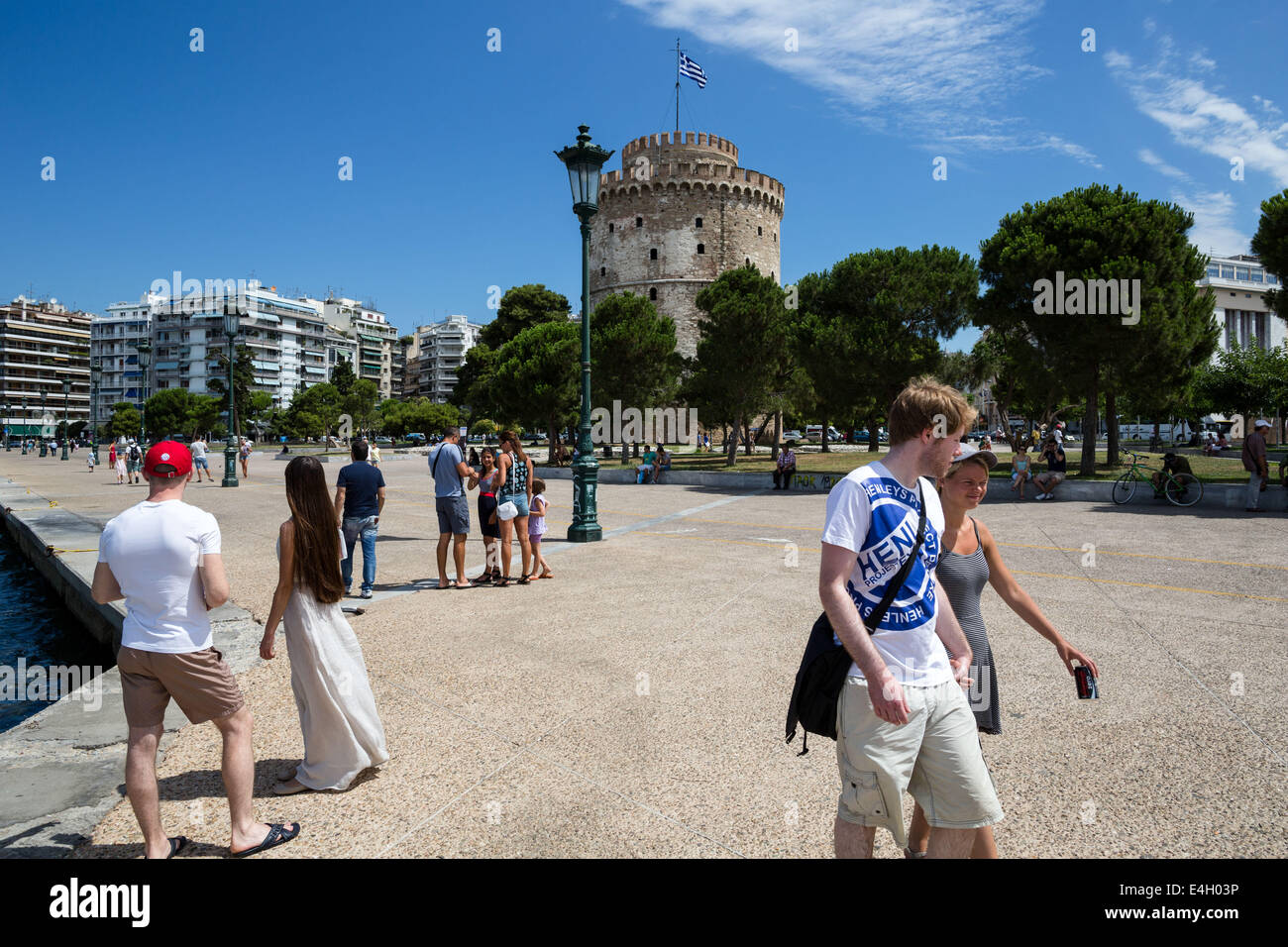 Thessaloniki, Greece. 11th July 2014. Tourists walk in front of city's landmark, the White Tower, on the seaside - Stock Image