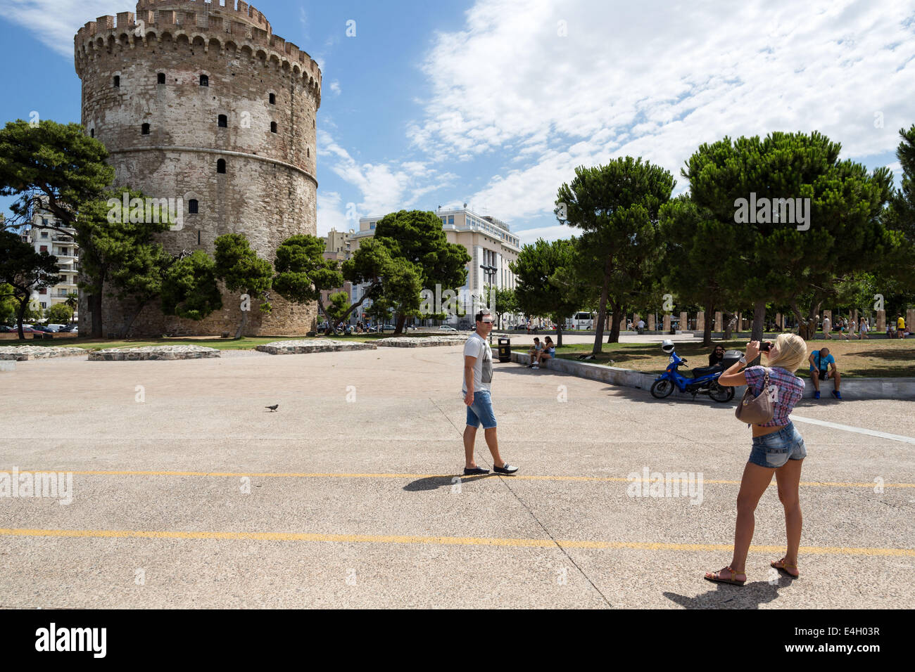 Thessaloniki, Greece. 11th July 2014. A tourist takes photos of city`s landmark, the White Tower, at the seafront - Stock Image