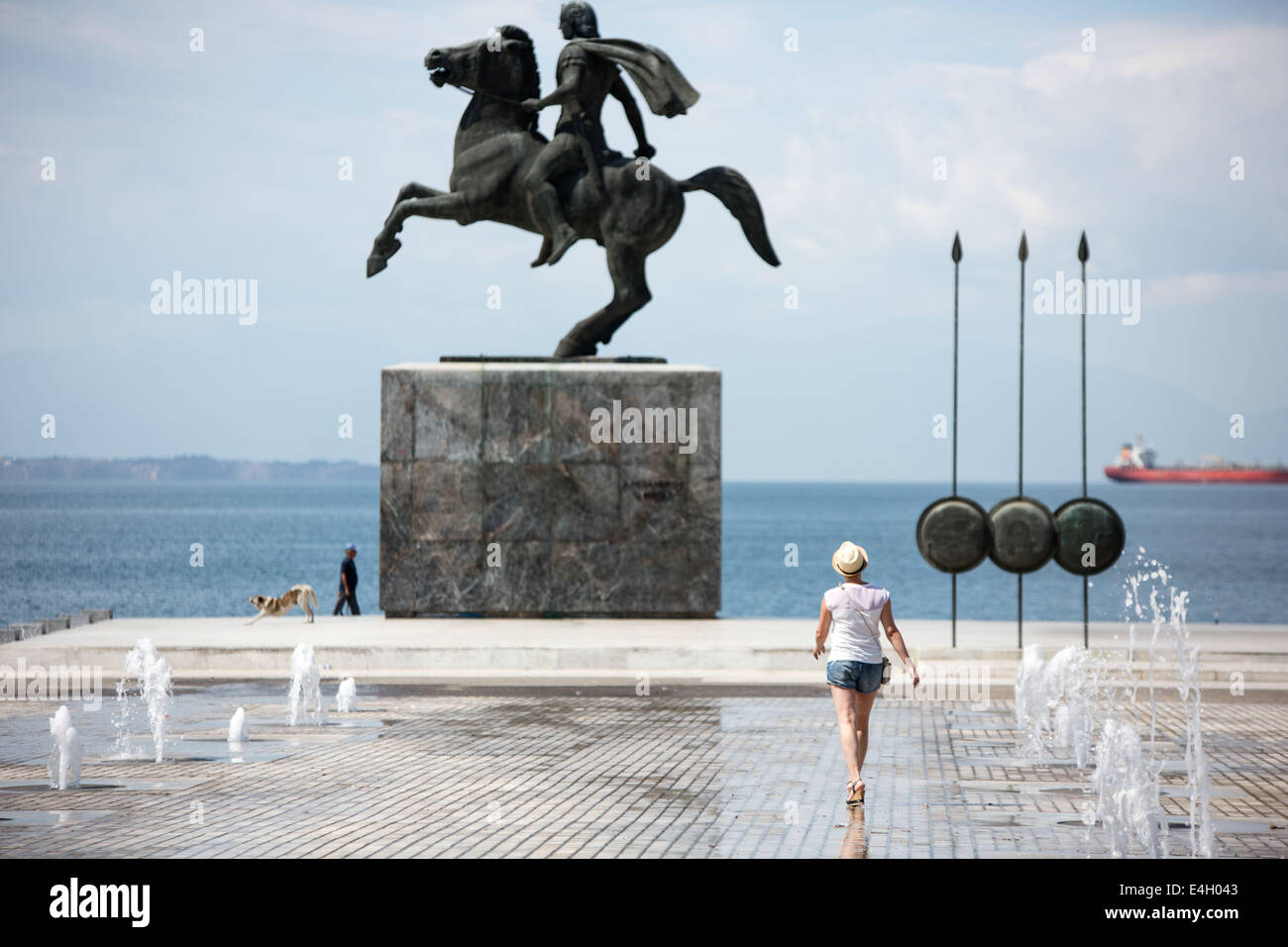Thessaloniki, Greece. 11th July 2014. Tourist in front of a statue of Alexander the Great and his horse Bucephalus, - Stock Image