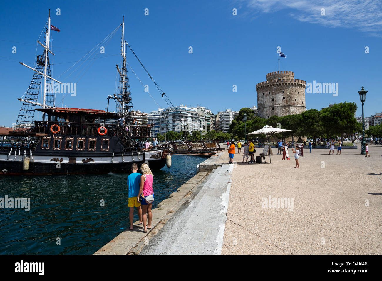 Thessaloniki, Greece. 11th July 2014. Tourists disembark from a cafe-bar boat in front of city's landmark, the - Stock Image