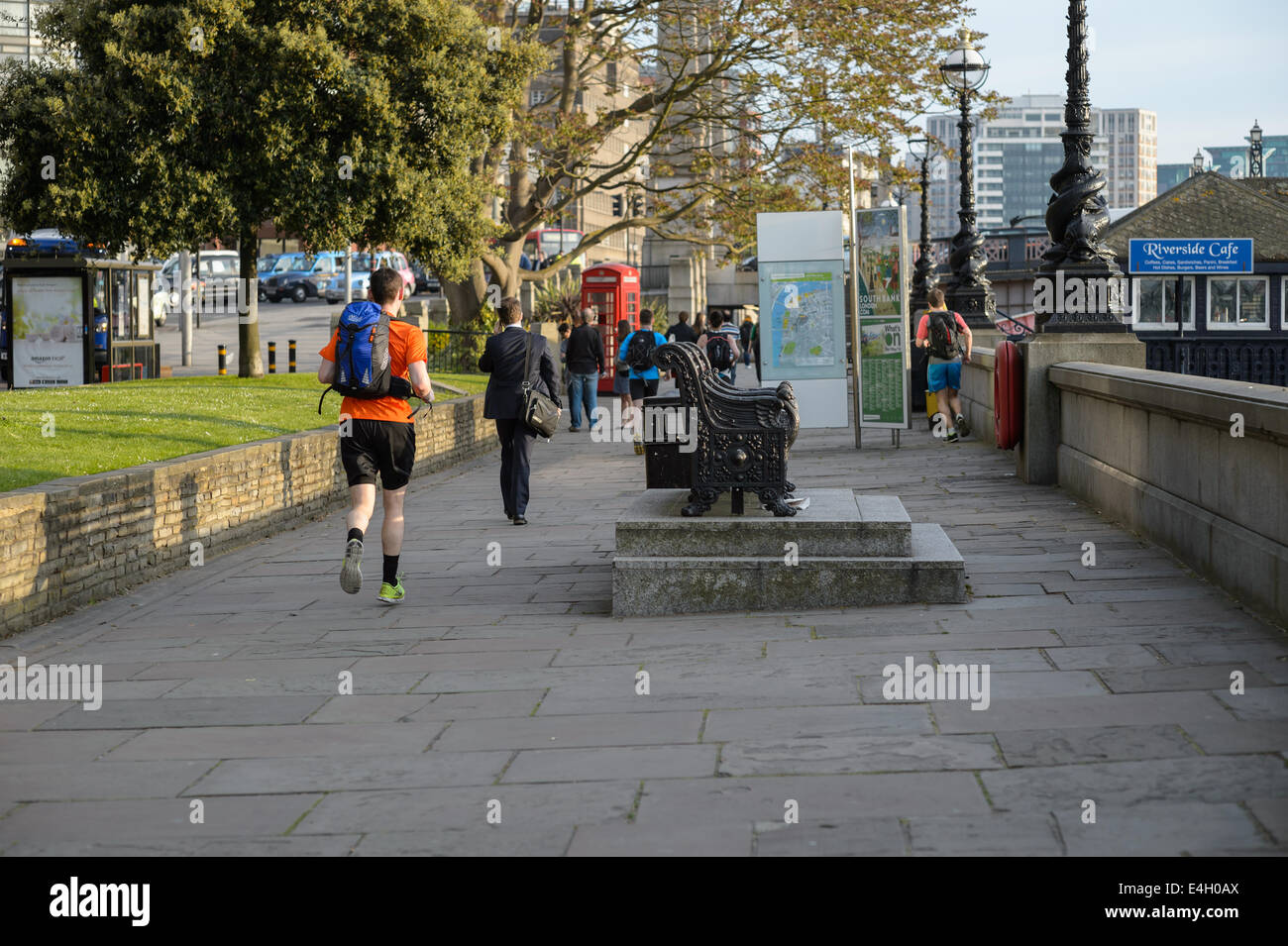 A jogger joggers runs run running home from work along the promenade on the south bank of the River Thames, Lambeth, - Stock Image