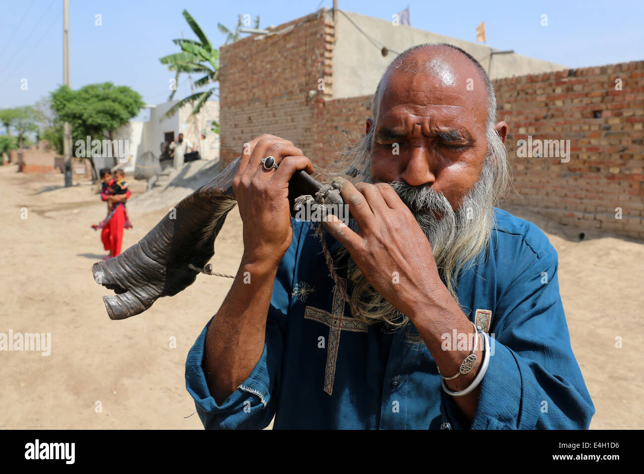 Man blowing on a goats horn, Khushpur village, Punjab, Pakistan - Stock Image