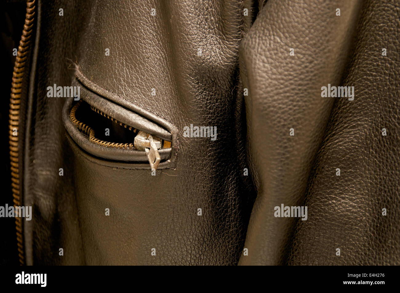 A black leather jacket fills the frame with focus on old rusted zippered pocket. - Stock Image