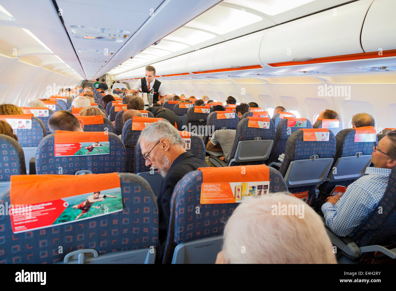 Steward serving passengers in flight in an Easyjet Aircraft. - Stock Image