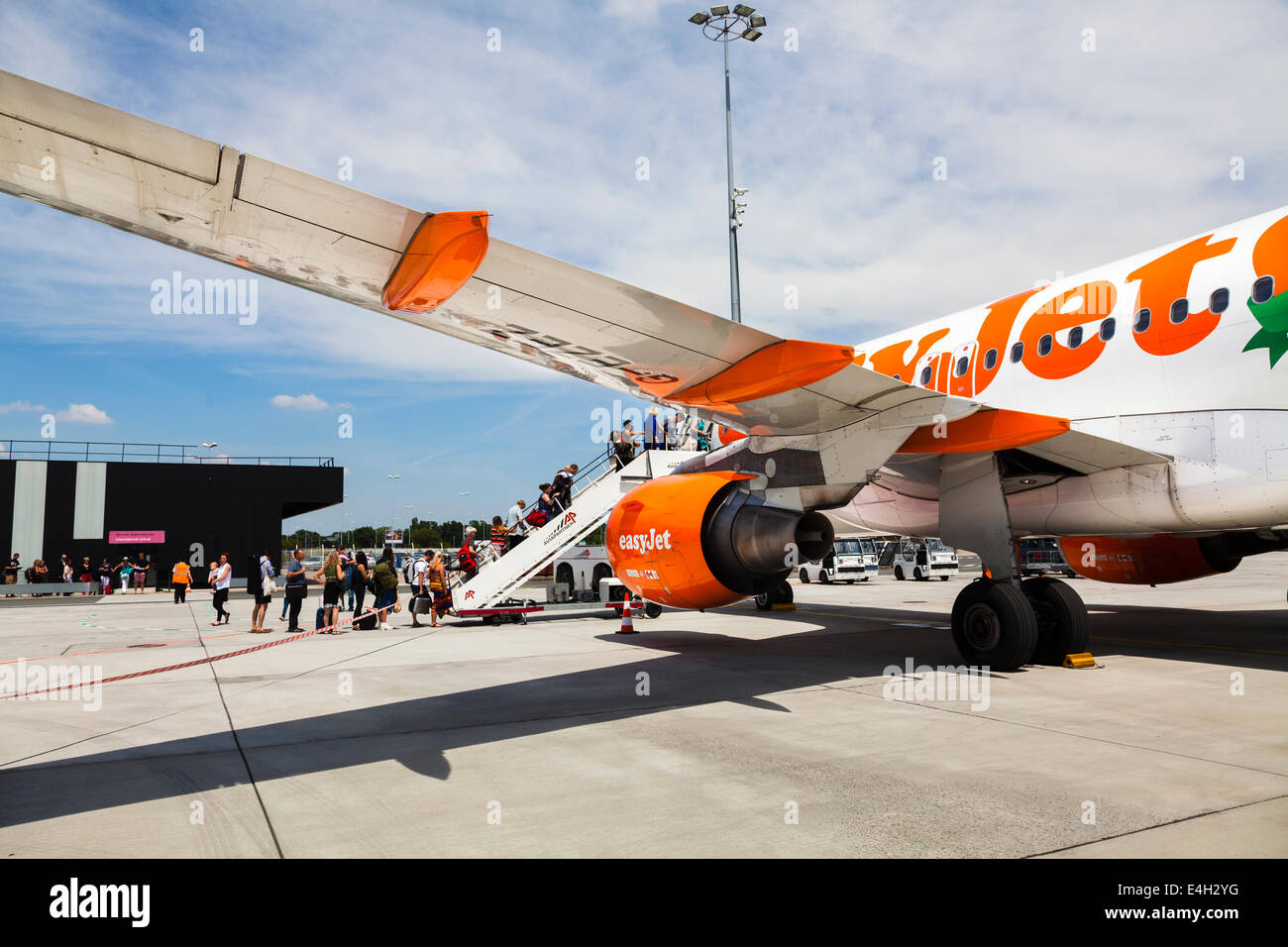 Passengers boarding via front stairs to Easyjet plane. - Stock Image