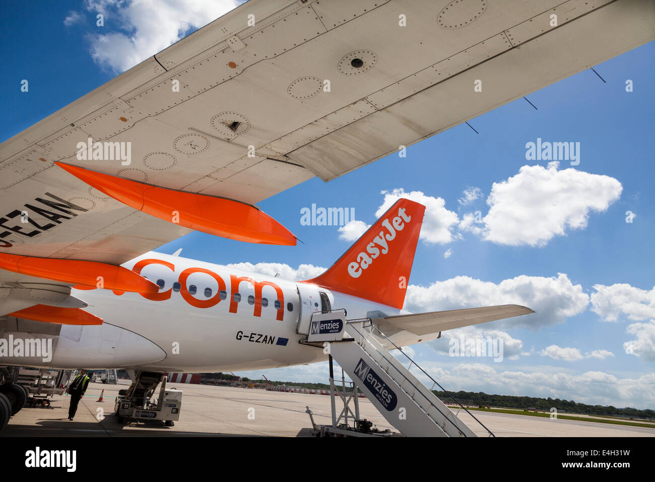 Under the wing of an EasyJet aircraft ready for boarding. - Stock Image