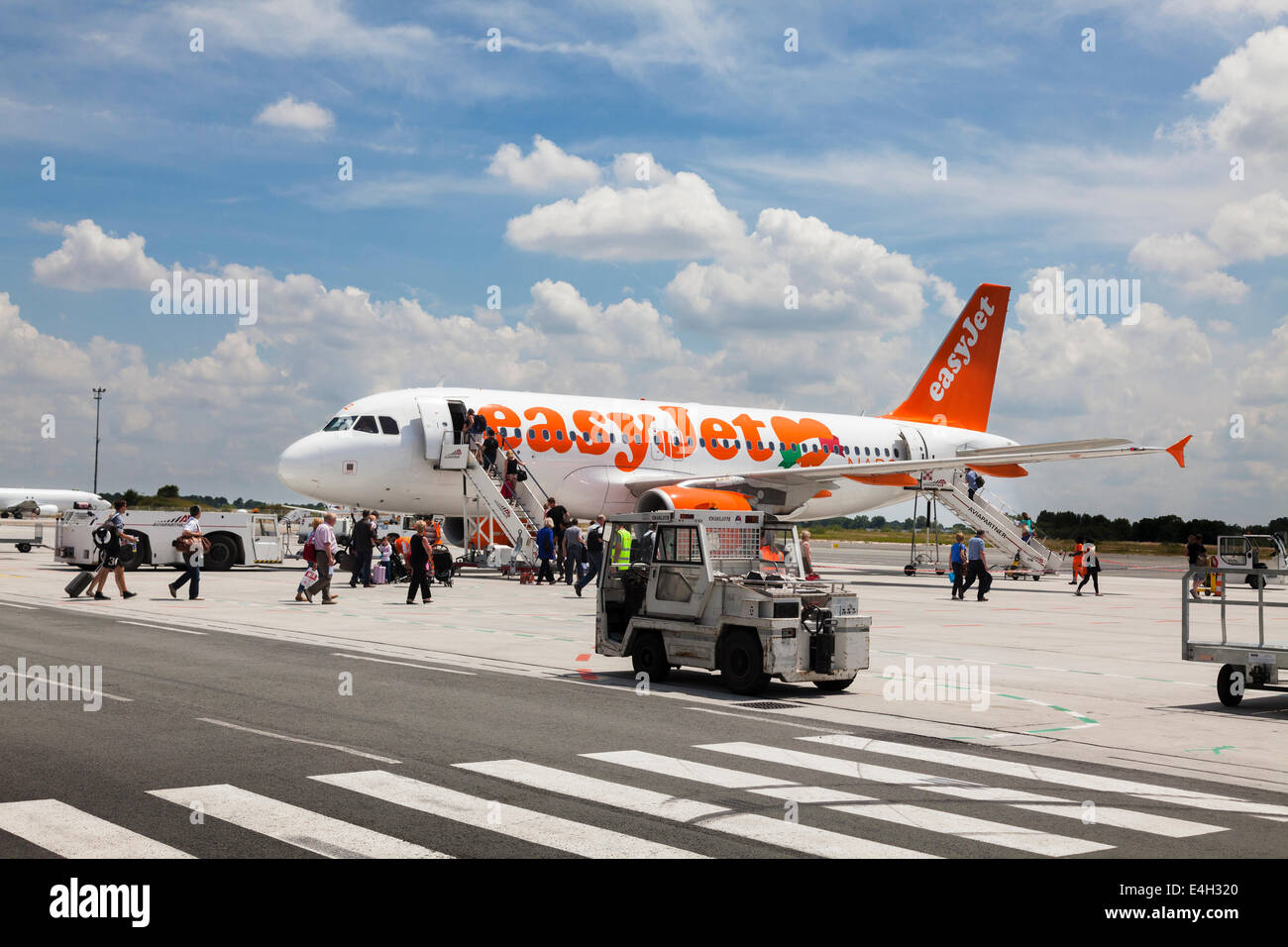 Passengers walking to Easyjet Aircraft for boarding. - Stock Image