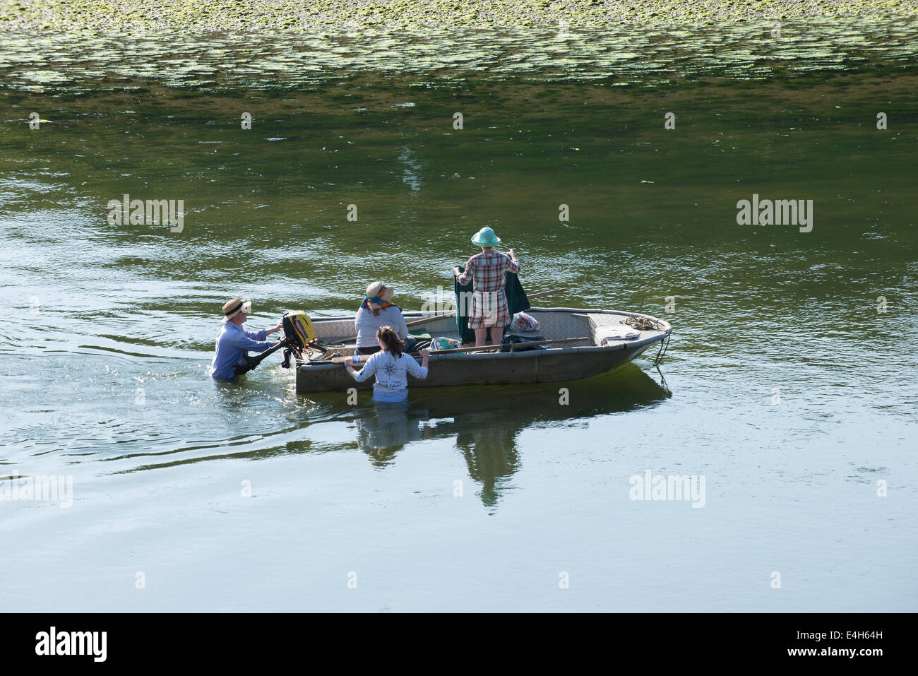 Family and boat at low tide on the River Erme South Devon England UK - Stock Image