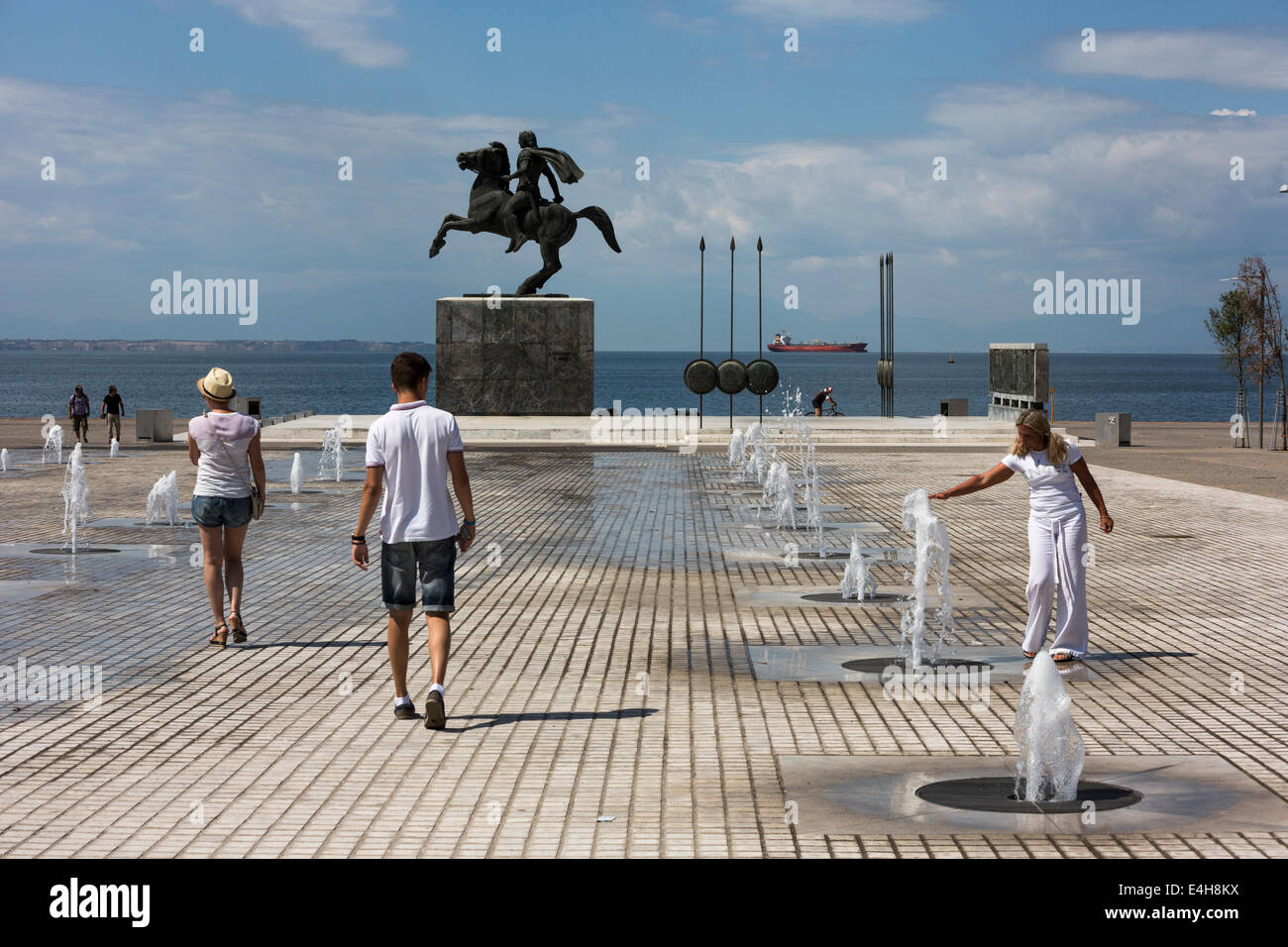 Tourists walk in front of a statue of Alexander the Great and his horse Bucephalus, during a sunny morning, in the - Stock Image