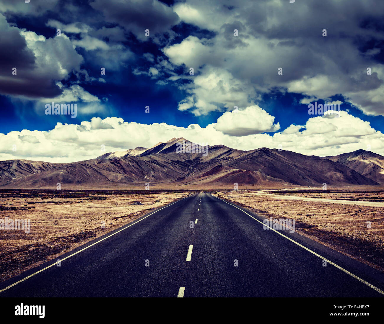 Vintage retro effect filtered hipster style travel image of Travel forward concept background - road on plains in - Stock Image