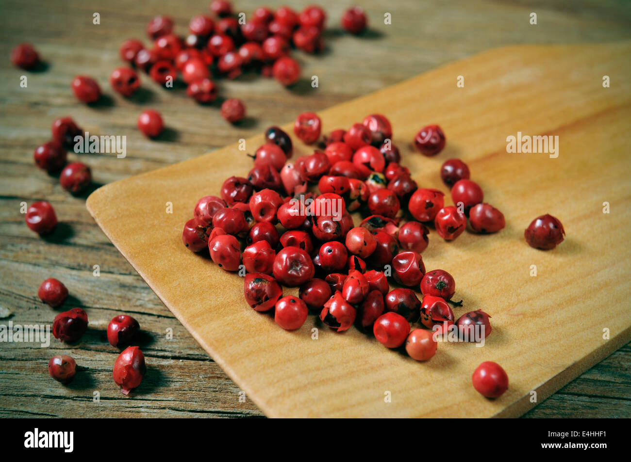 a pile of pink peppercorns on a rustic wooden table - Stock Image
