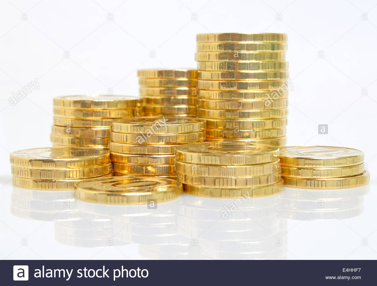 Stacks of coins on a light surface. - Stock Image