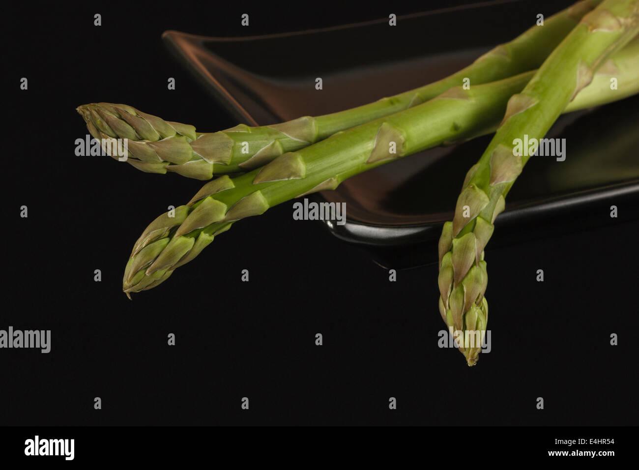 Three fresh Asparagus on black Dish - Stock Image