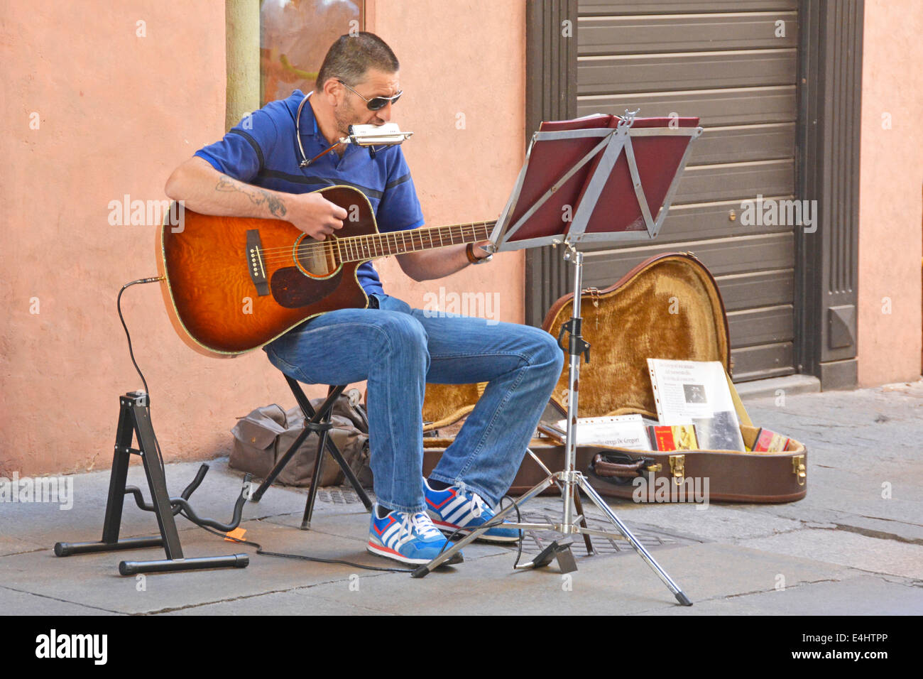 Street musician busker sitting beside a small display of his recorded music Ravenna Emilia Romagna Italy - Stock Image