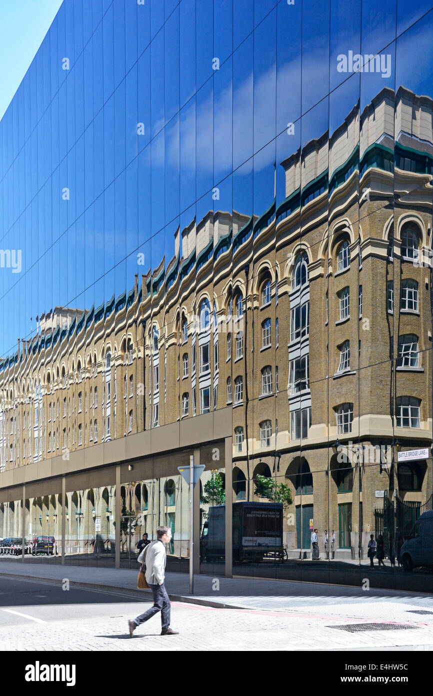 Bricks and mortar building reflected in glass walls of new modern office block - Stock Image