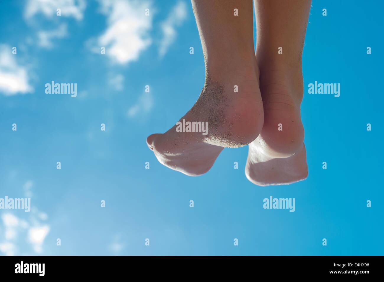 Children's feet against the blue sky - Stock Image
