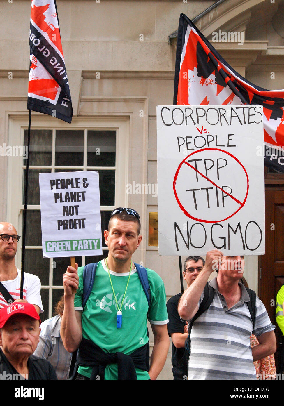 London, UK. 12th July, 2014. Activists hold a Green Party placard  and Corporates vs People placard during the anti - Stock Image