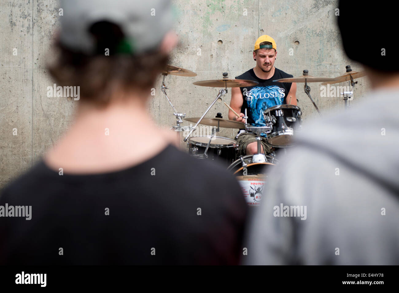 A drummer street performer plays to an audience in the Piccadilly Gardens area of Manchester City Centre. - Stock Image