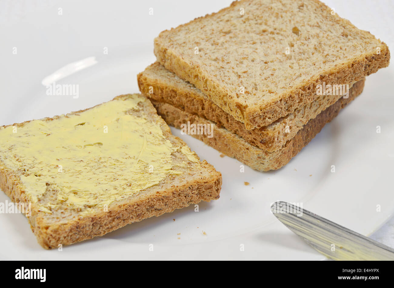 four slices of toast and butter with knife on white plate, close up, full frame - Stock Image