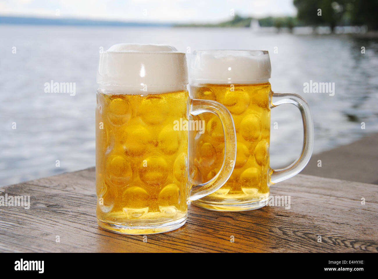 two beer mugs with fresh beer and foam on a wooden table in a beer garden on lake, close up - Stock Image