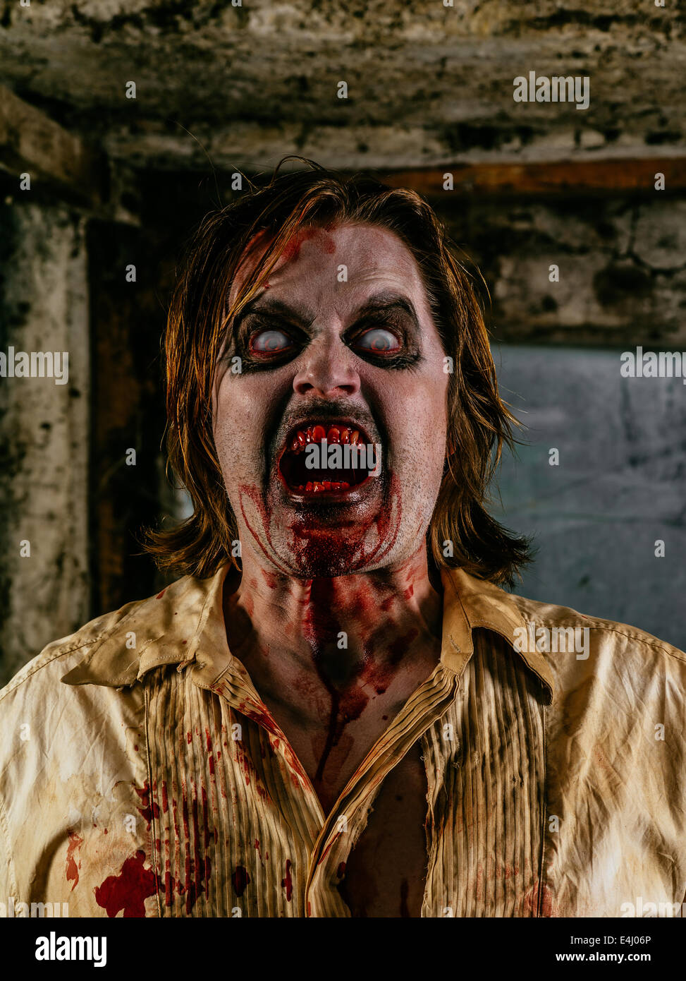 Photo of a hungry zombie covered with blood about to attack you. - Stock Image