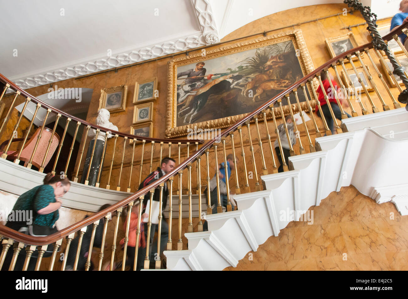 People Walking Up An Ornate Staircase In A Stately Home With Many Polished  Brass Spindles