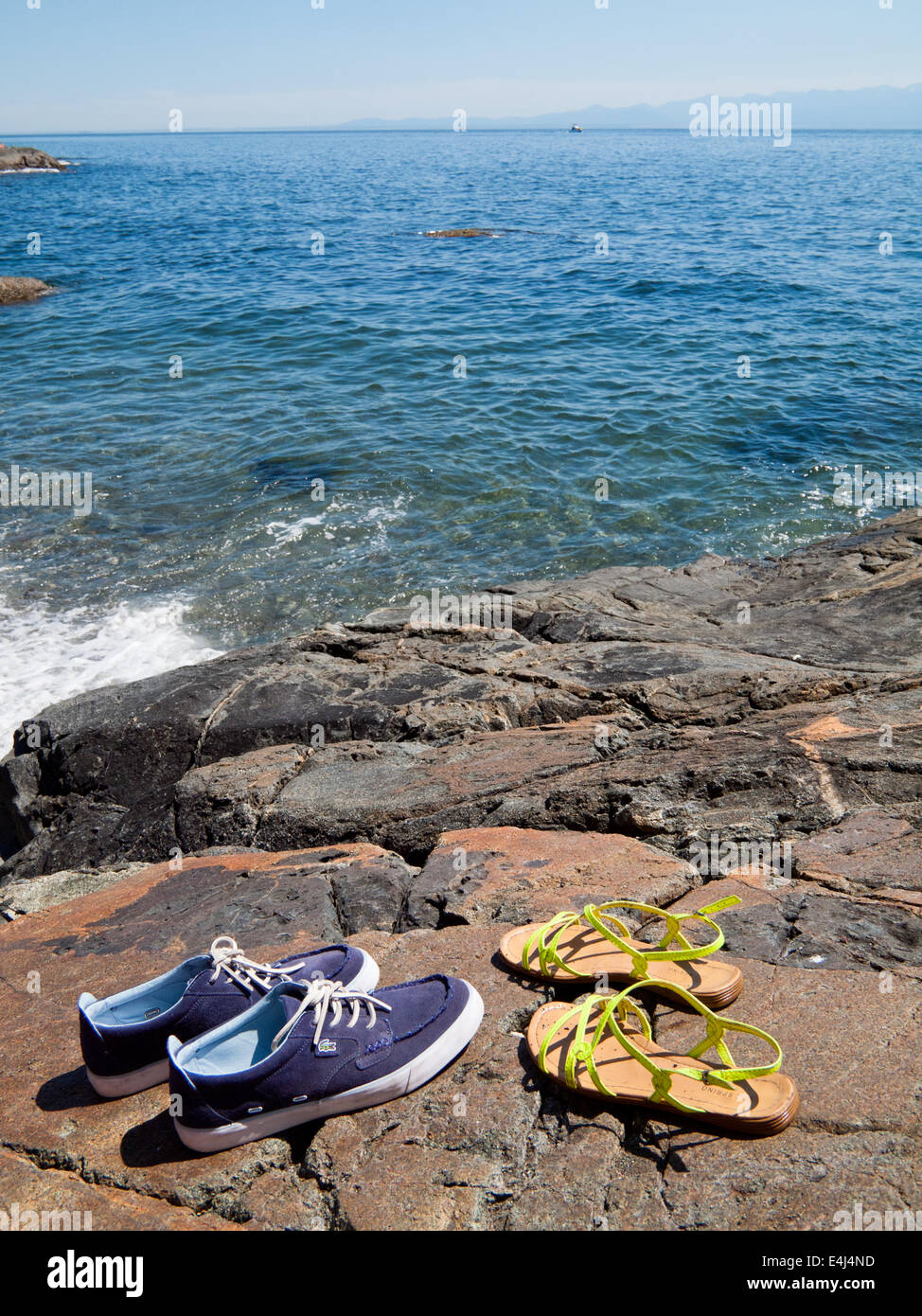 His and hers. Mens' boat shoes and ladies' sandals by the sea.  Victoria, British Columbia, Canada. - Stock Image