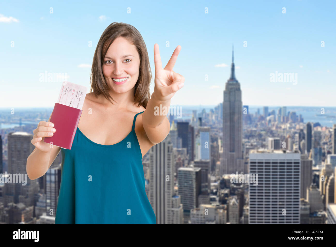 Happy young woman holding plain tickets and a passport, isolated in white - Stock Image