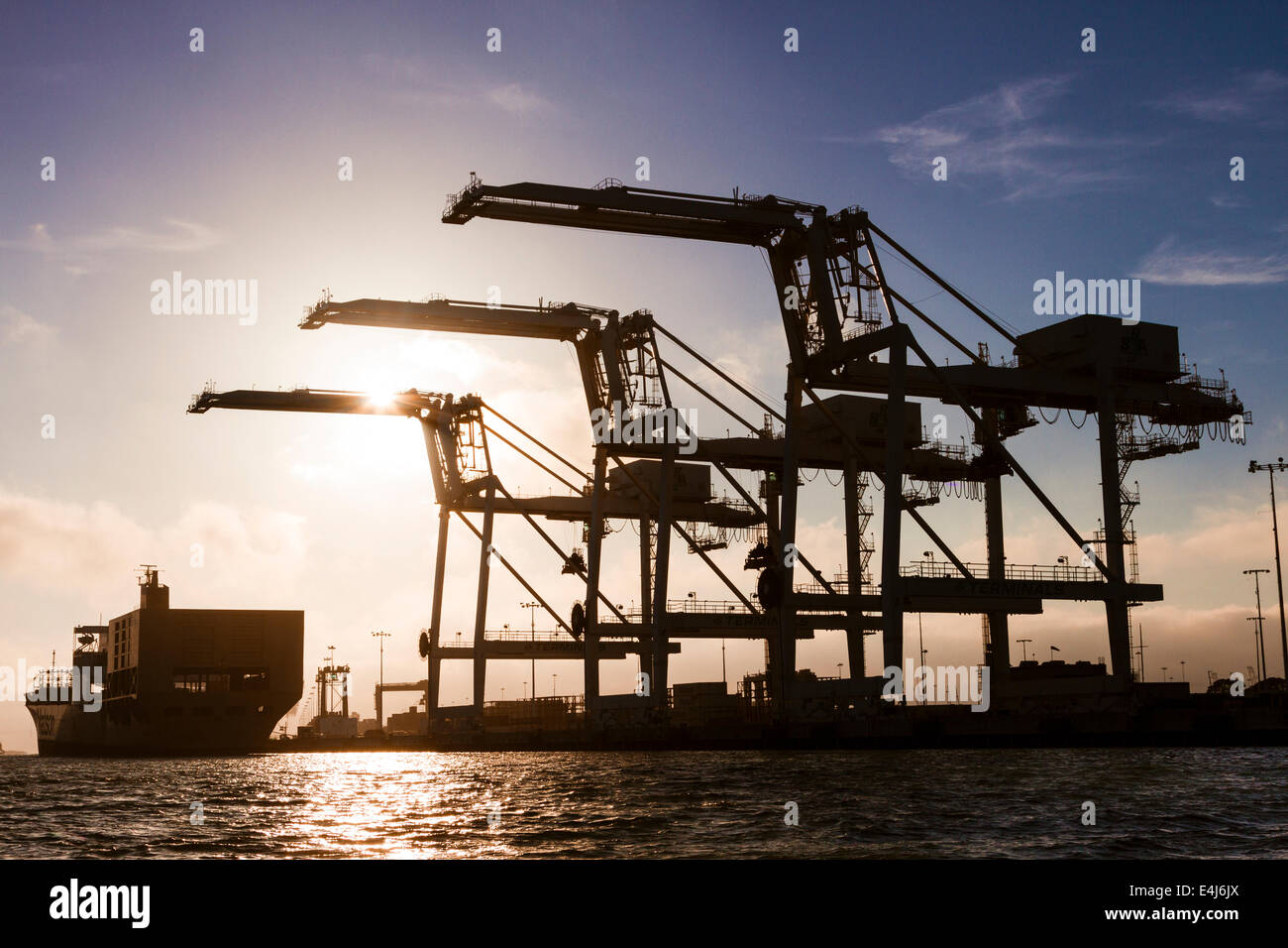 Cargo container ship approaching three giant container cranes at the Port of Oakland intermodal container terminal Stock Photo