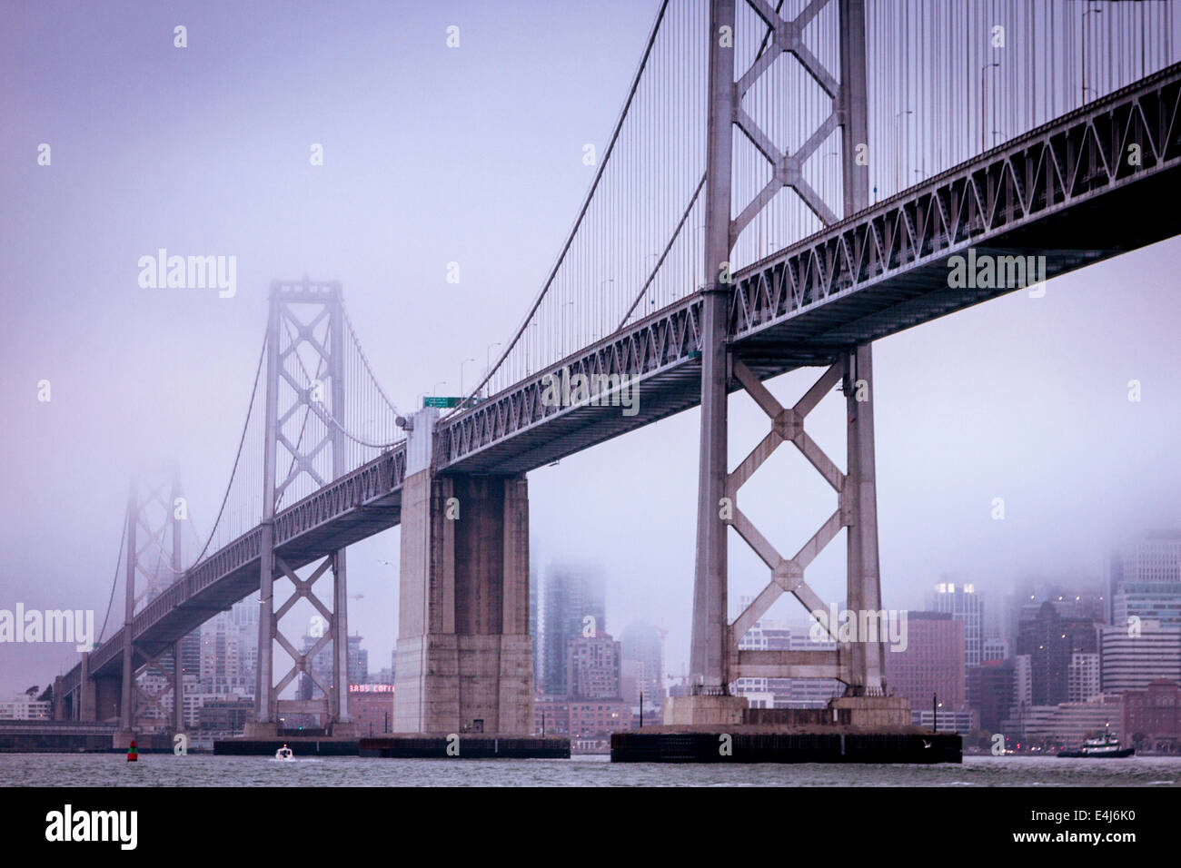 San Francisco Bay Bridge and the city from the water on a cold and foggy day - Stock Image
