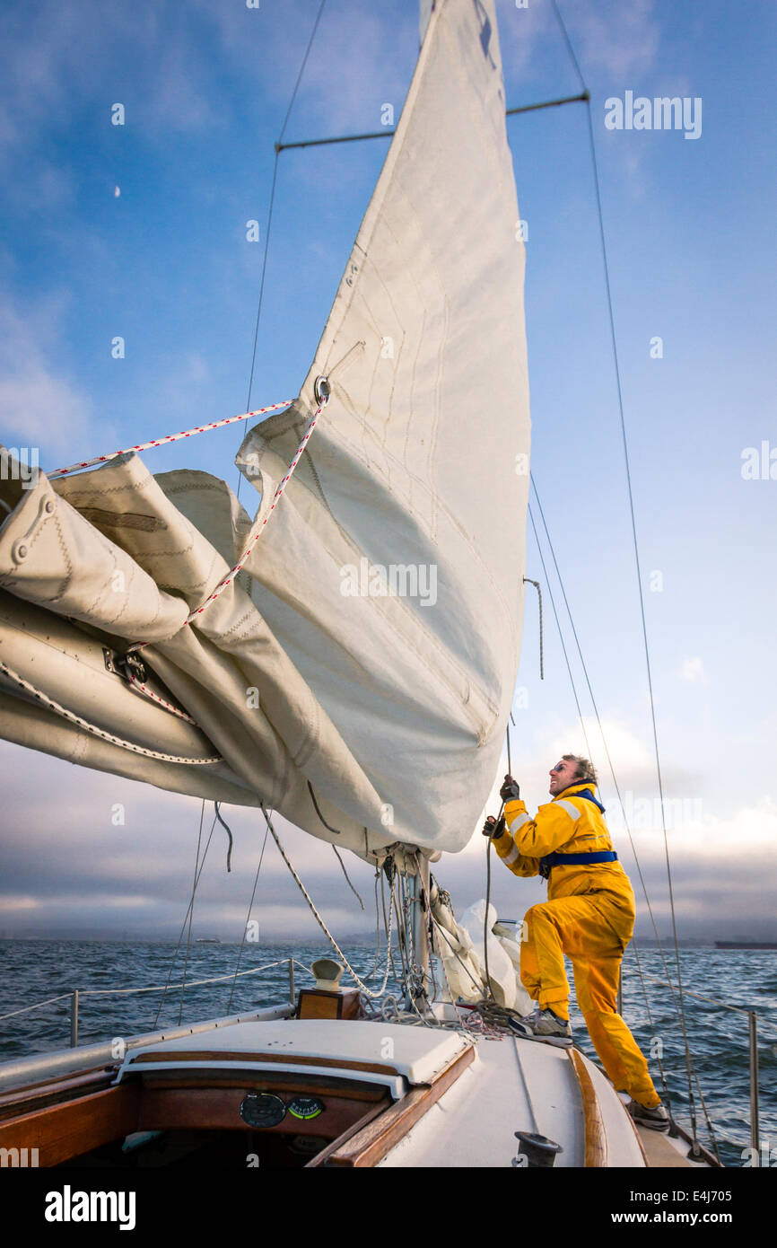 Sailor in yellow foul weather gear pulling on the halyard to raise the mainsail as he heads into cloudy weather - Stock Image
