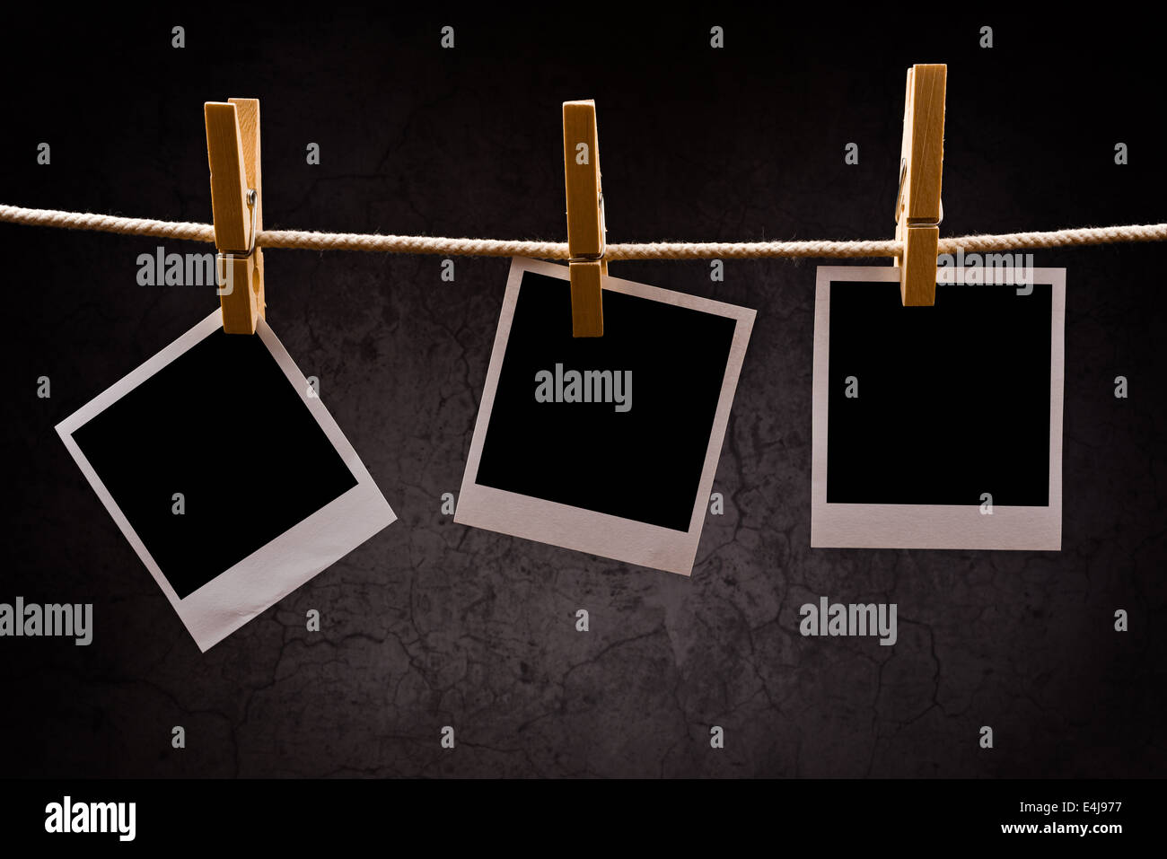 Photography paper with instant photo frames attached to rope with clothes pins. Copy space for your image. - Stock Image