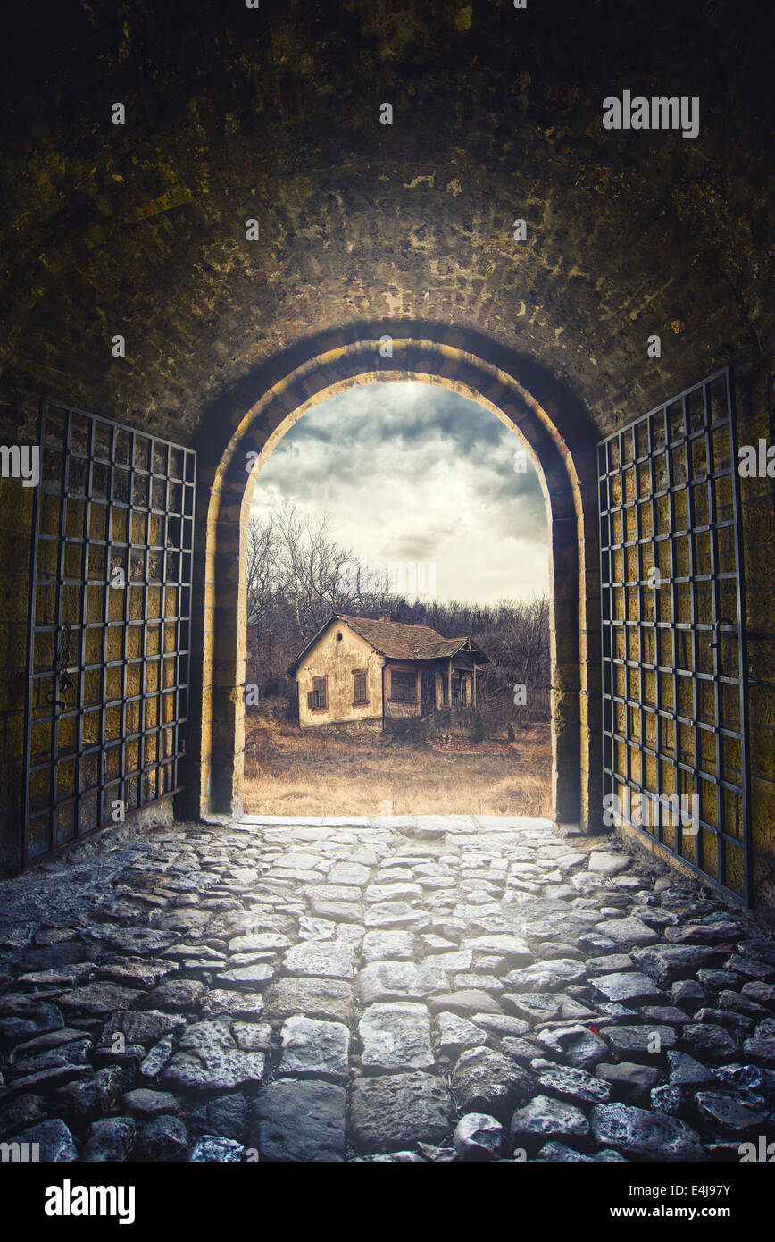 Arch Gate opening to road leading an old abandoned house.Old childhood memories. - Stock Image