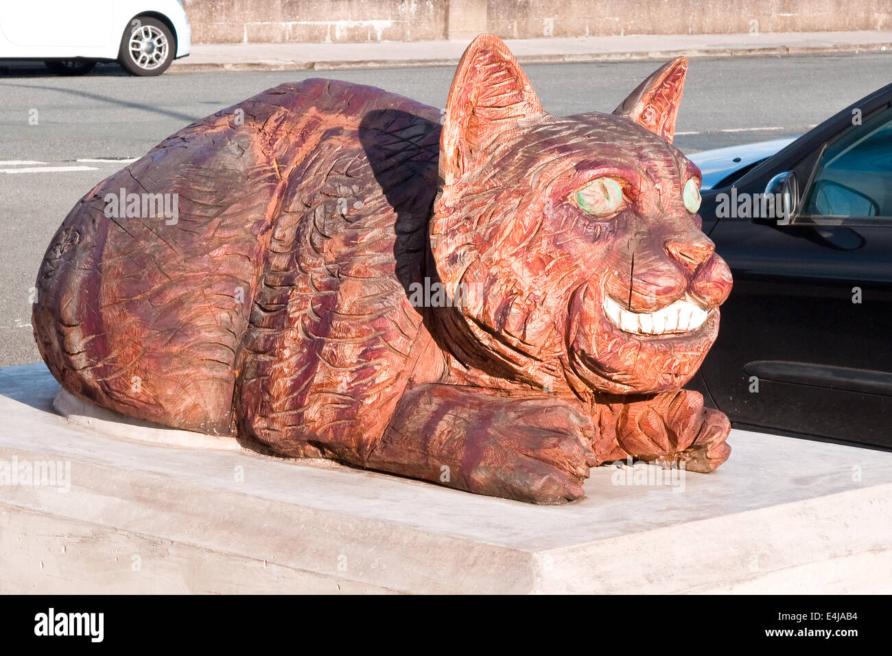 Wooden carving of the Cheshire Cat, one of a series of Lewis Carroll characters displayed in Llandudno, North Wales - Stock Image