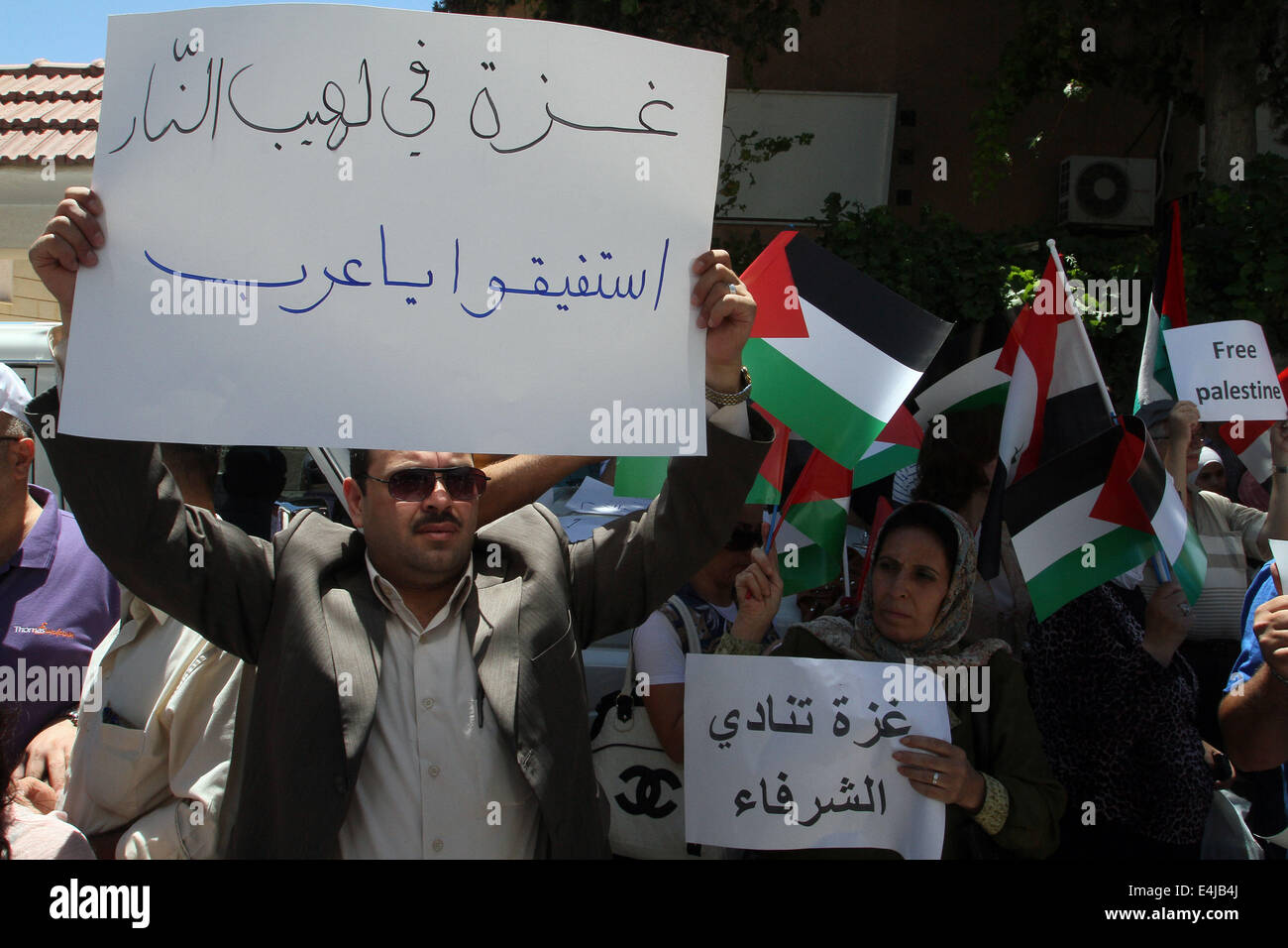 Damascus. 13th July, 2014. Hundreds of Syrian protesters hold anti-Israel banners as well as the Syrian and Palestinian - Stock Image