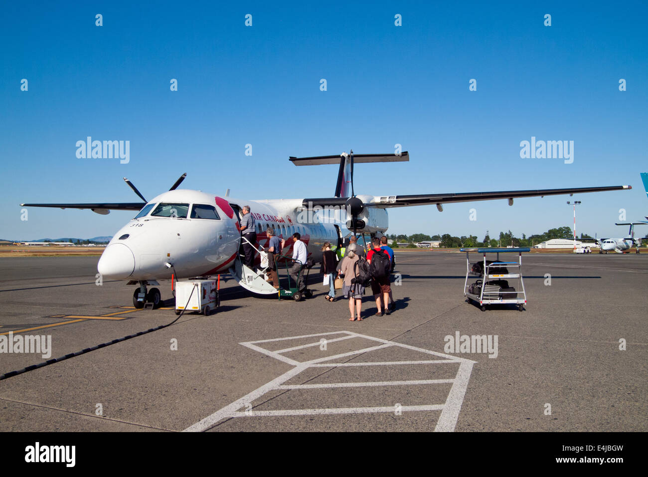 Passengers board an Air Canada Jazz Bombardier Dash 8-300 (DH3) at Victoria International Airport (YYJ) in Victoria, - Stock Image