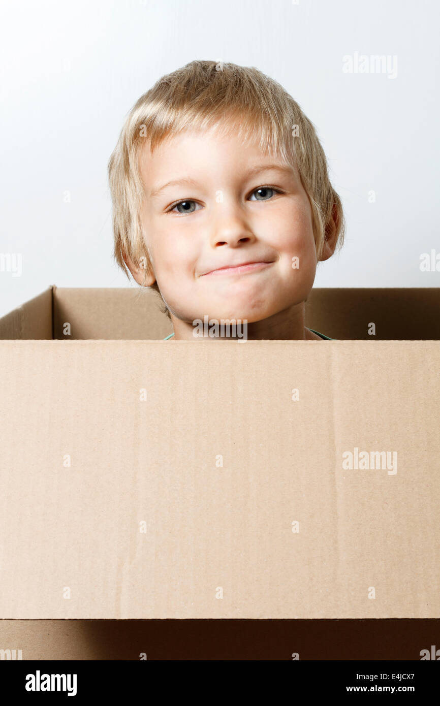 Young boy inside a cardboard box. - Stock Image