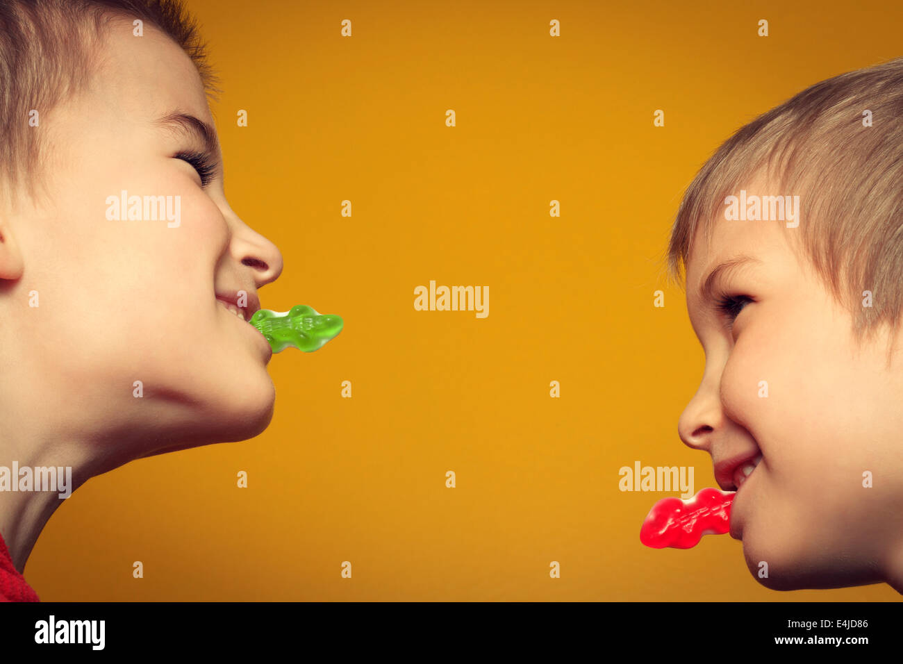 Young boys facing each other while eating candy. - Stock Image