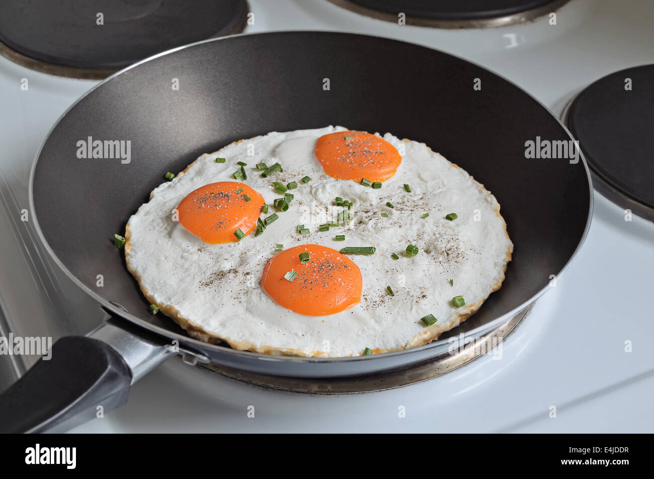 fried eggs with three yolks and chive in a frying pan, close up - Stock Image