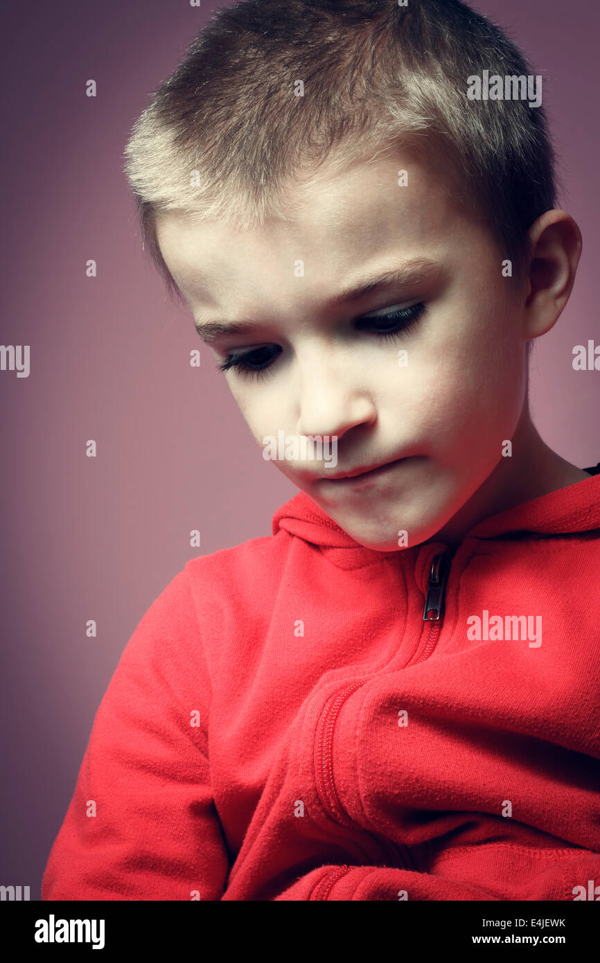 Young boy indoors thinking. - Stock Image