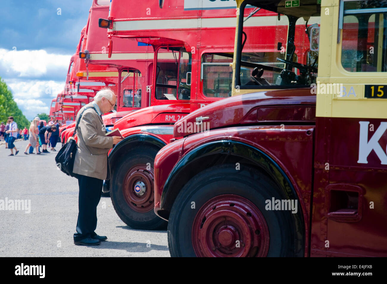 An enthusiast notes down the registrations of red routemaster buses at the Routemaster Bus Festival in Finsbury - Stock Image